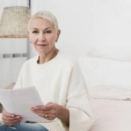 Imagem mostra aposentada com os papéis da revisão de aposentadoria