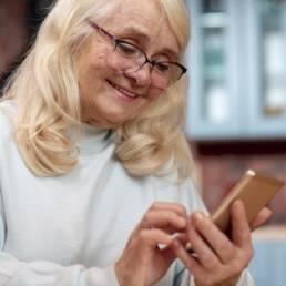 Imagem mostra senhora idosa fazendo a prova de vida pelo celular